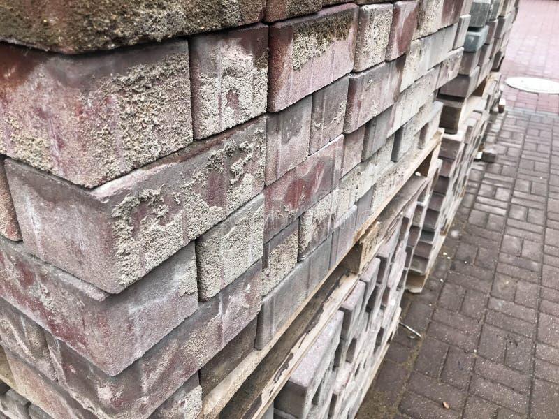 Rote Zementfliese des Pflastersteins für das Legen des Straßenbaus, Pflasterung auf hölzernen Paletten an einer Baustelle lizenzfreie stockfotografie