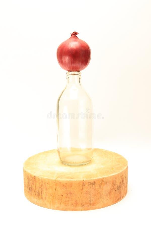 Rote Zwiebel auf klarer Flasche auf asiatischem traditionellem Schneidebrett lizenzfreie stockbilder