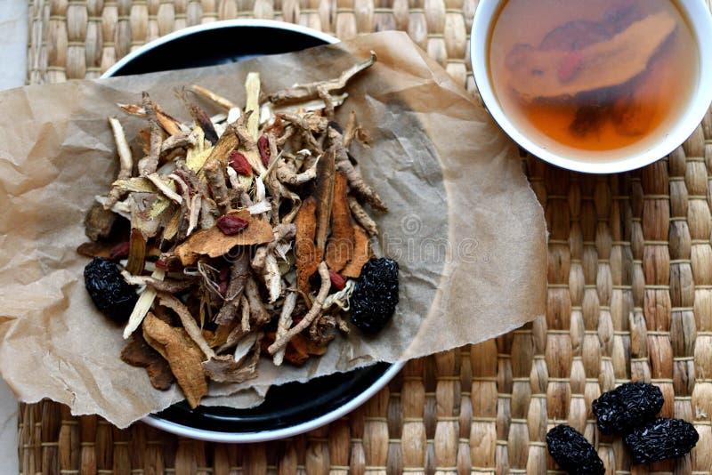 Roteiro chinês da medicina tradicional Tisana com jujuba, bagas do goji, raizes do gingseng e outro no papel de pergaminho no neu foto de stock royalty free
