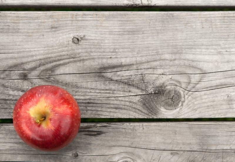 Roter Apfel auf alter hölzerner Tabelle von oben lizenzfreie stockfotografie