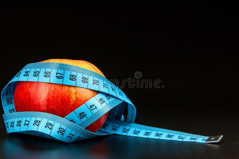 Roter Apfel Roter Apfel eingewickelt im Maßband eines Schneiders auf einem schwarzen Hintergrund Das Konzept des Gewichtsverlusts stockfoto