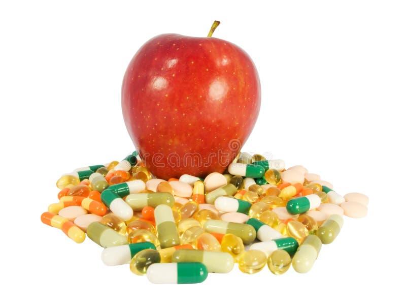 Roter Apfel gegen Pillen stockfotografie
