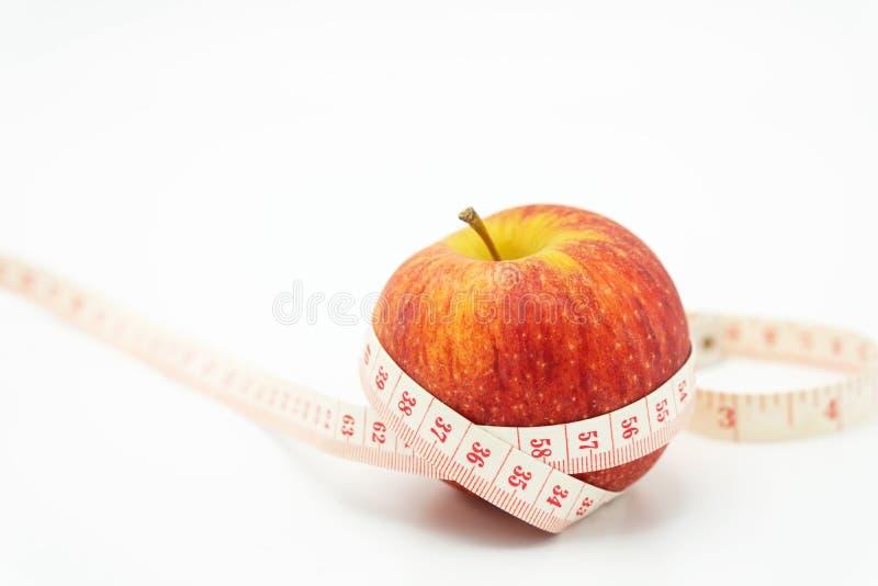 Roter Apfel herum eingewickelt mit Maßband Gesunde Frucht zum hereinzulegen lizenzfreie stockfotos