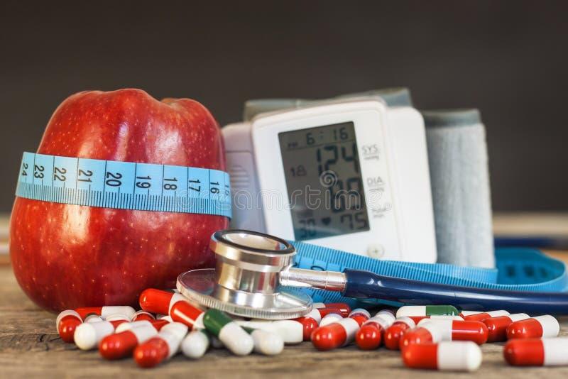 Roter Apfel mit dem messenden Band, zum von Länge zu messen Behandlung von Korpulenz und von Diabetes, Blutdruckmessung stockfotografie