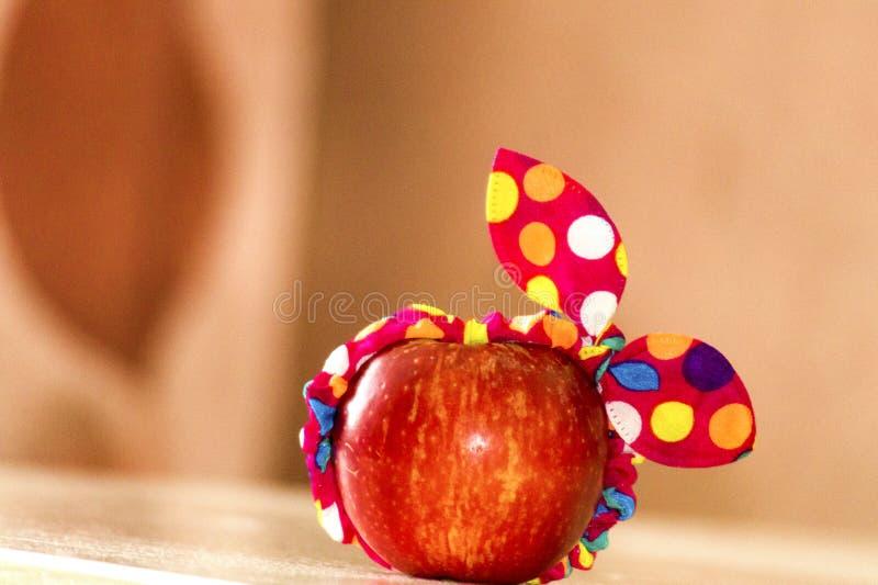 Roter Apfel mit einem gro?en Hintergrund, ein Apfel liegt auf einer Tabelle, ein Apfel in einem Verband, ein lustiger Apfel, Mini stockbilder
