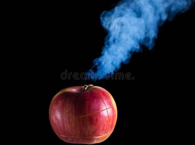 Roter Apfel mit Schnitten auf einem schwarzen Hintergrund raucht stockfotos
