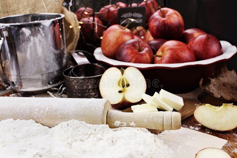 Roter Apfel, Nelken und Zimtsteuerknüppel auf einem Ausschnittvorstand lizenzfreies stockfoto