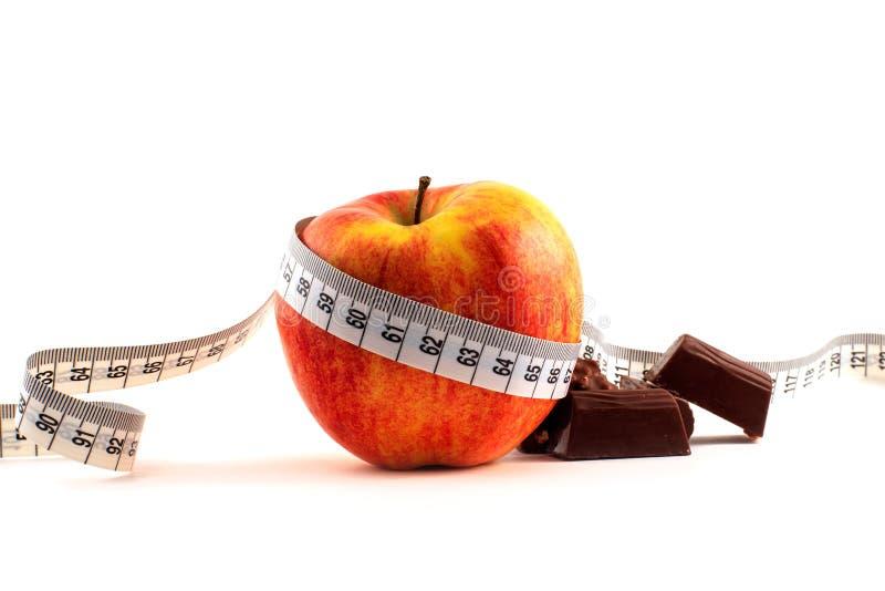 Roter Apfel, Schokolade und messendes Band stockbild
