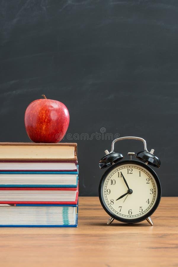 Roter Apfel und Wecker auf Schulbank für zurück zu Schule lizenzfreies stockbild