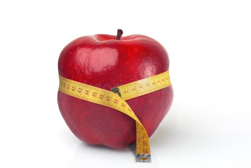 Roter Apple zusammengedrückt durch Bandmaß stockfoto