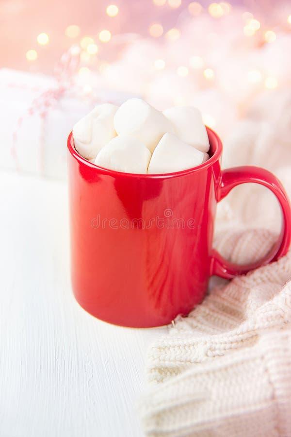Roter Becher mit heiße Schokoladen-Kakao-Getränk und Eibische auf die Oberseite Funkelndes Funkeln Garland Lights im Hintergrund  stockfotografie