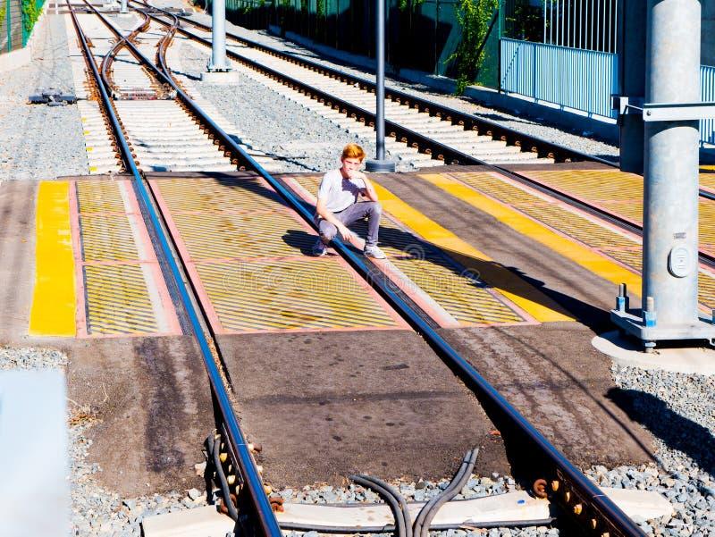 Roter behaarter Junge duckte sich über hellem Schienen-Zebrastreifen nahe bei Metro-Licht-Schienen-Plattform stockfotos