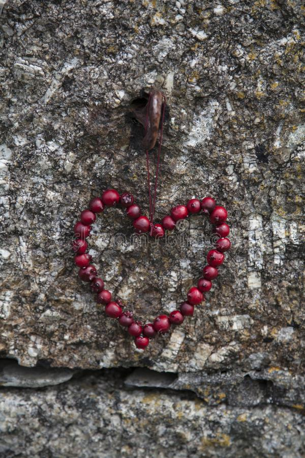 Roter Berry Heart On Stone Wall stockfotografie