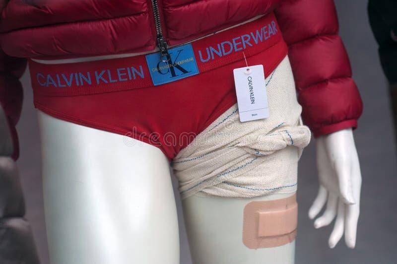 Roter Bikini Calvin Kleins auf dem Mannequin, das in Mode roten Speicherausstellungsraum des Wintermantels für Frauen trägt lizenzfreies stockbild