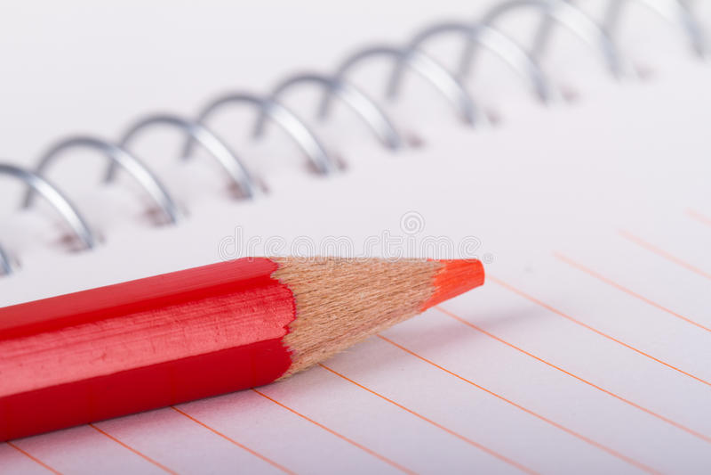 Roter Bleistift auf Notizbuch lizenzfreie stockfotografie
