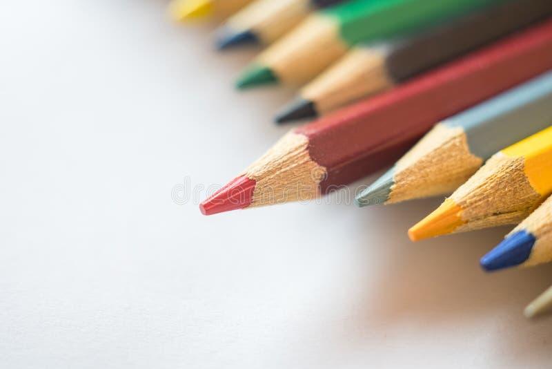 Roter Bleistift, der heraus von anderen Farbbleistiften steht lizenzfreies stockbild