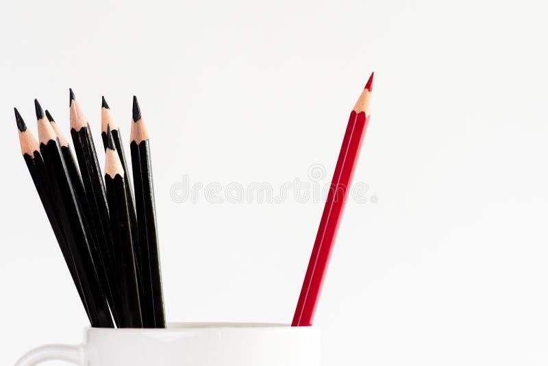 Roter Bleistift trennte sich in der blauen Schale mit unter schwarzem Bleistift stockfoto