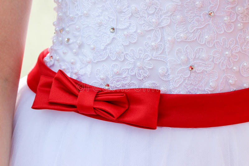 Roter Bogen auf Hochzeitskleid stockfotografie