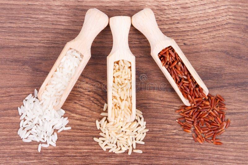 Roter, brauner und weißer Reis mit hölzerner Schaufel auf rustikalem Brett stockfotos