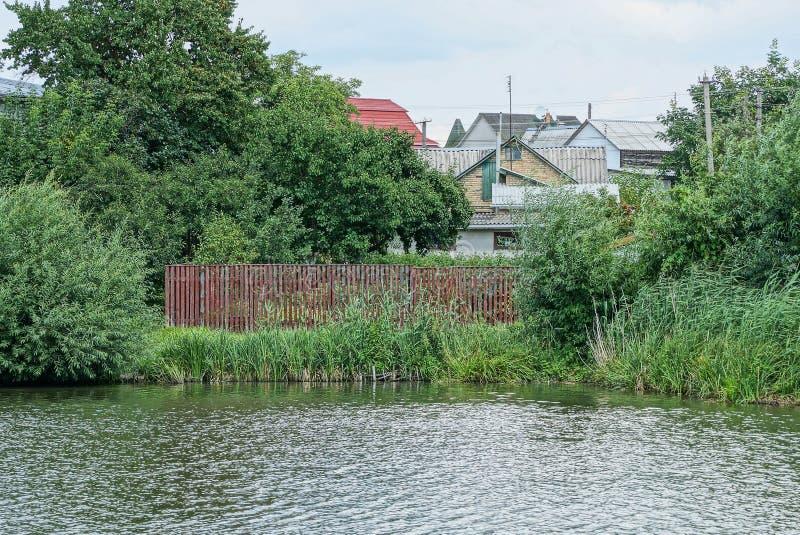 Roter Bretterzaun überwältigt mit Schilfen und grüner Vegetation auf dem Ufer des Reservoirs nahe dem Wasser stockfotos