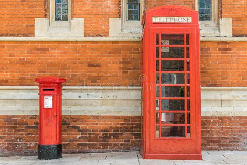 Roter Briefkasten und eine rote Telefonzelle und eine Wand des roten Backsteins lizenzfreie stockfotografie