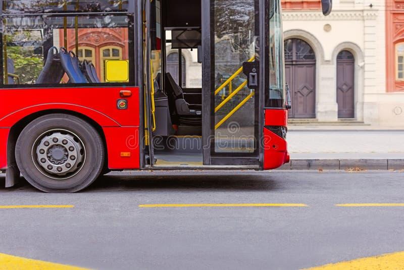 Roter Bus des öffentlichen Transports auf Bushaltestelle an der Straße lizenzfreie stockfotografie
