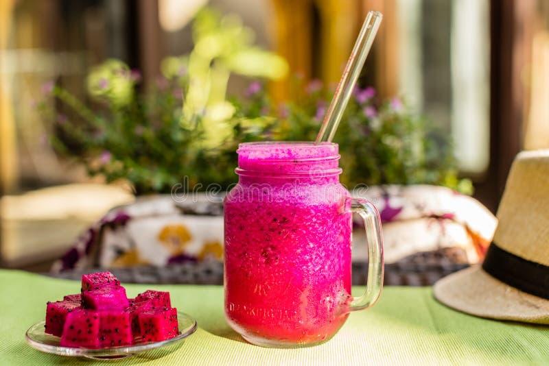 Roter DracheFruchtsaft in einem Glas mit einem Glasstroh, Hut, geschnittene Drachefrucht auf einer Glasplatte Blumen auf einem Hi lizenzfreie stockfotografie