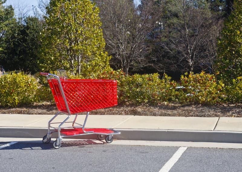 Roter Einkaufswagen im Parkplatz stockfoto
