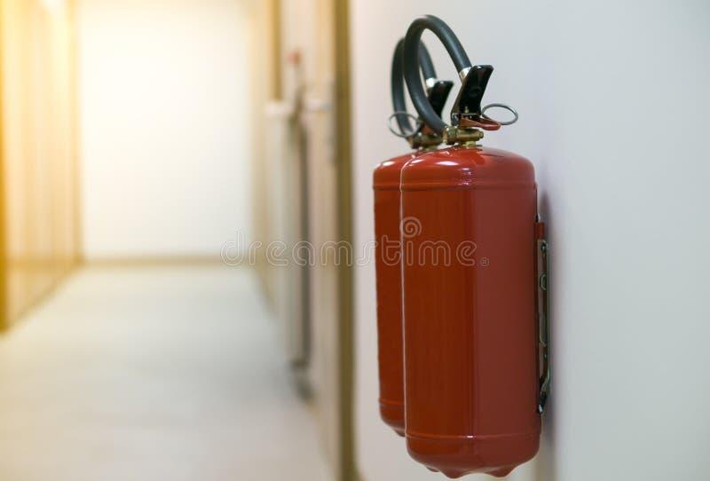 Roter Feuerlöscher im leeren Korridor auf der weißen Wand mit Sonnenaufflackern lizenzfreie stockbilder