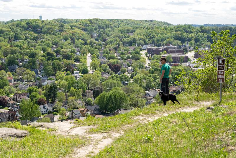 Roter Flügel, Minnesota - 25. Mai 2019: Wanderermann, der seine Hunderisiken weg auf einer ungebilligten Spur, trotz der Warnzeic stockfotos