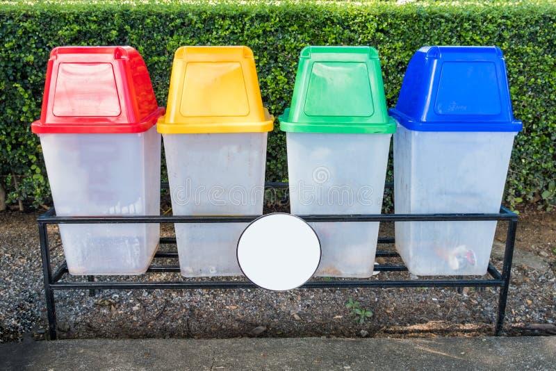Roter, gelber, grüner, blauer Plastik mit Kappenpapierkörben im Park stockfotos