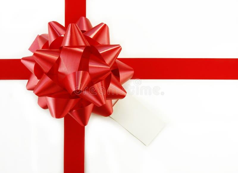 Roter Geschenk-Bogen und Marke auf weißem Kasten lizenzfreies stockbild