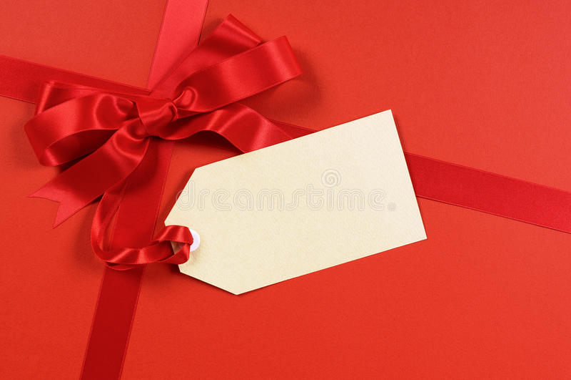 Roter Geschenkband-Bogenhintergrund mit leerem Tag oder Manila-Aufkleber, Kopienraum lizenzfreies stockfoto
