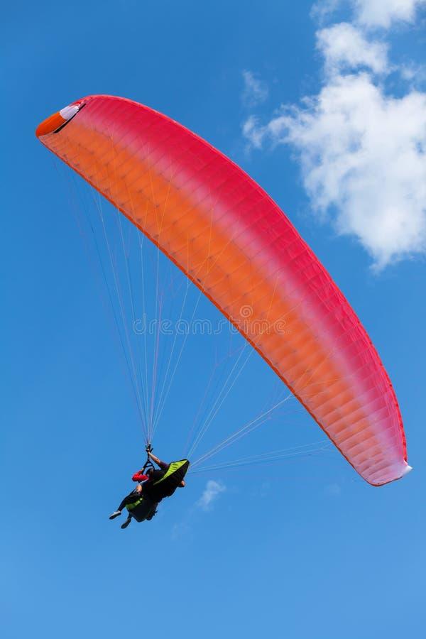 Roter Gleitschirm im blauen Himmel lizenzfreie stockfotos