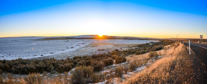 Roter Goldener Wintersonnenuntergang am Horizont des weitläufigen, hügeligen Bauernlandes auf der Autobahn unter dem dunklen Blau stockbild