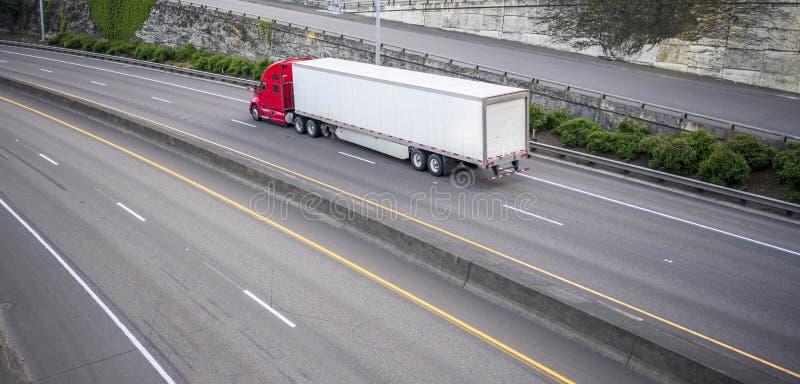 Roter großer LKW der Anlagenfernstrecke halb mit dem trockenen des Packwagens Anhänger halb, der auf geteilter breiter Landstraße stockfoto
