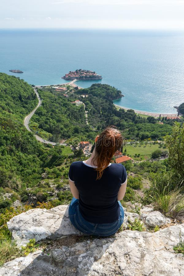 Roter Hauptmädchenhügel, der Insel Sveti Stefan in Budva, Montenegro genießt Junge Frau, die zum adriatischen Meer und zur grünen lizenzfreies stockfoto