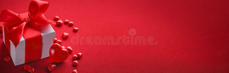 Roter heart-shaped Schmucksachegeschenkkasten und eine rote Spule auf einem Zeichen stockbild