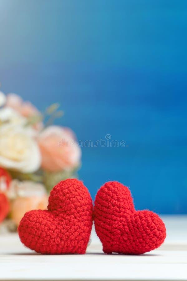 Roter heart-shaped Schmucksachegeschenkkasten und eine rote Spule auf einem Zeichen Hand machen zwei Garn rotes Herz vor rosafarb stockfotos