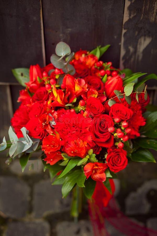 Roter Heiratsblumenstrauß auf einem dunklen Hintergrund lizenzfreies stockbild