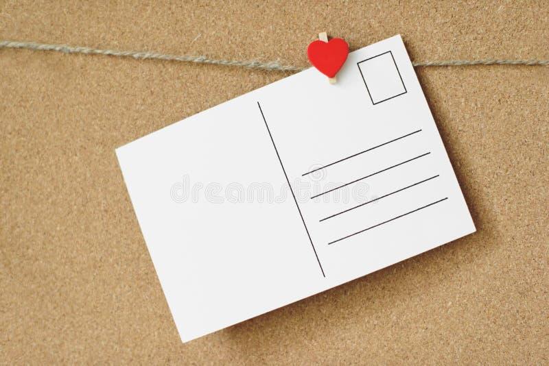 Roter Herzstift und weiße Postkarte mit Freiexemplarraum über braunem Handwerk bereiten Korkenbretthintergrund auf Valentinsgruß  stockbild