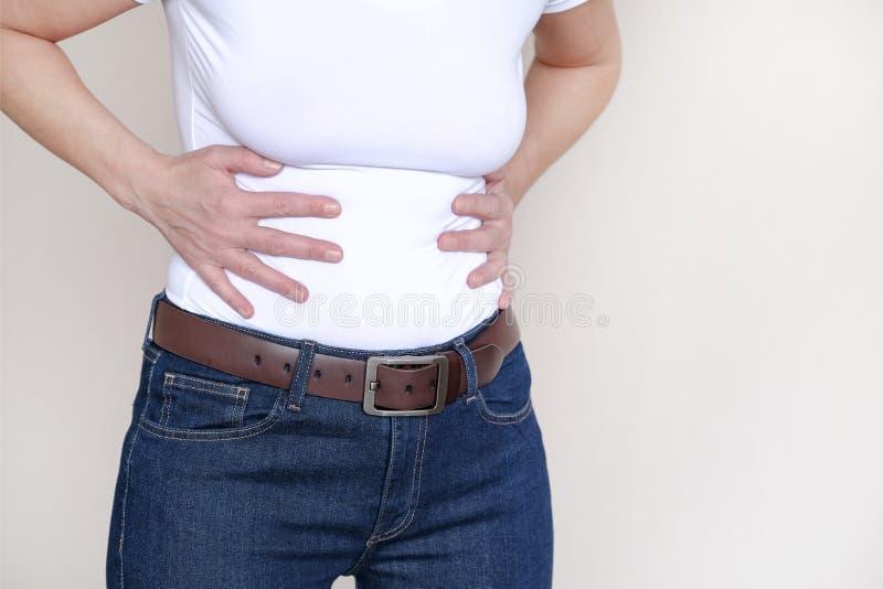 Roter Hintergrund des Schmerzbereichs Eine Frau, die unter Bauchschmerzen leidet Gesundheitsproblem Frauenhändchenhalten auf ihre stockfotografie