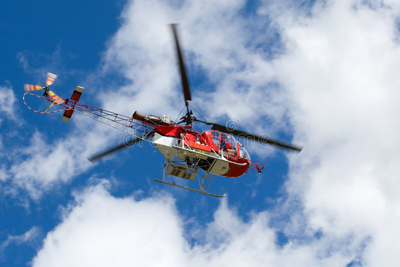 Roter Hubschrauber auf dem blauen Himmel lizenzfreies stockfoto