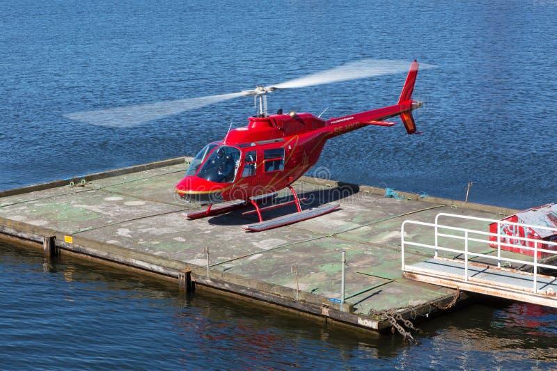 Roter Hubschrauber, der über das Wasser von Stockholm fliegt stockfotografie