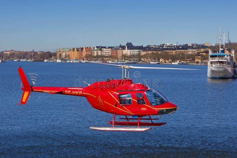 Roter Hubschrauber, der über das Wasser von Stockholm fliegt stockbilder