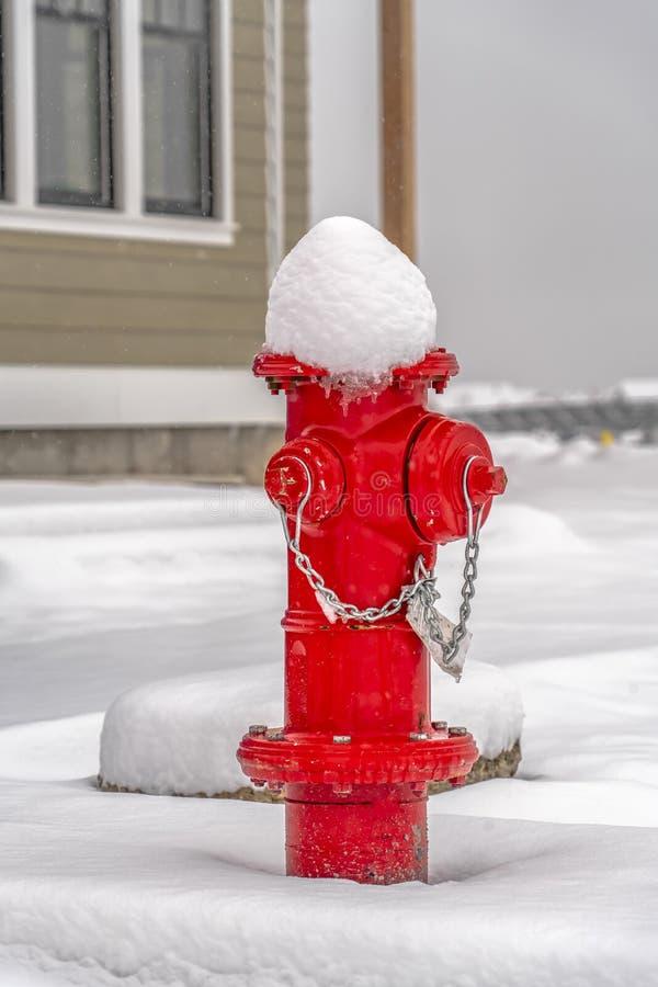 Roter Hydrant auf dem Boden mit einer Decke des Schnees lizenzfreie stockbilder