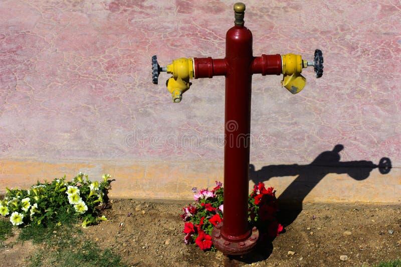 Roter Hydrant mit gelben Verbindungsstücken Hydrant oder Feuerlöschpumpe, stellt den Punkt der Verbindung dar, durch den Feuerweh lizenzfreies stockfoto