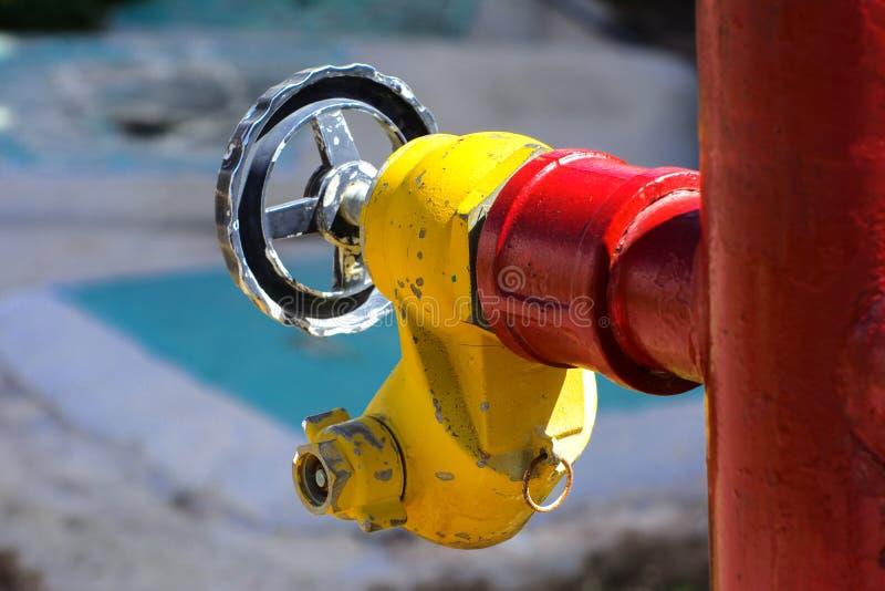 Roter Hydrant mit gelben Verbindungsstücken Hydrant oder Feuerlöschpumpe, stellt den Punkt der Verbindung dar, durch den Feuerweh stockbild