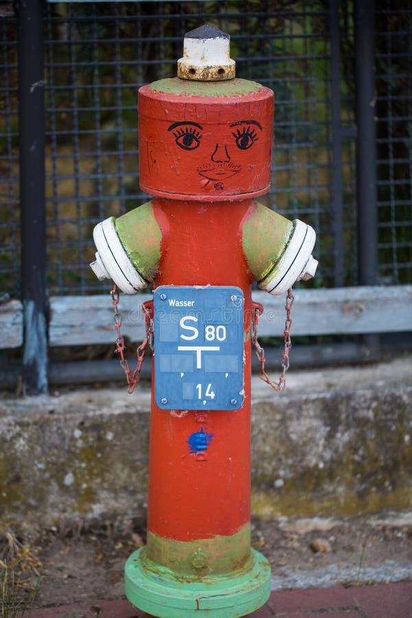 Roter Hydrant mit Gesicht lustiger Hydrant, Gartenzaun als backgrou lizenzfreies stockfoto