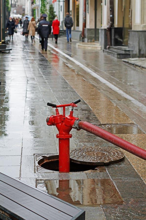 Roter Hydrant mit Schlauch in der Luke lizenzfreie stockfotografie